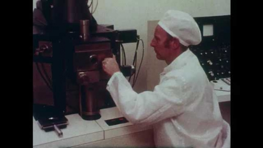 1980s: Man in lab, man inserts slide into microscope, zoom in. Man looks in microscope. Magnified view of microprocessor.