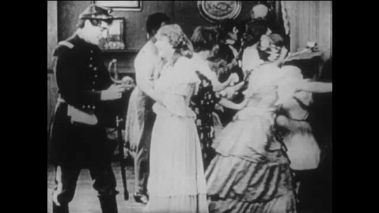 1910s: men and woman celebrate as Northern soldiers parade past house as man in Union soldier uniform walks with girl in dress to grass lawn, sit on stones, hold hands, stand up and enter house.