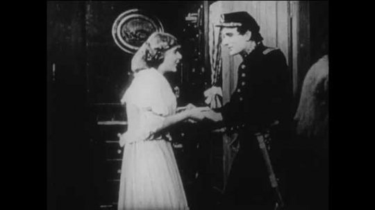 1910s: woman in dress and man in Union uniform hold hands, hug, kiss and exit living room. man draws sword and leads march with parade of Northern soldiers with rifles on shoulders as women wave.