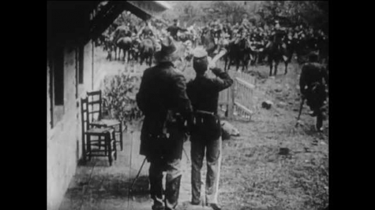 1910s: men in Union military uniforms line up behind stone walls, wave USA flag and fire rifles as officers wave swords. title card about panic stricken boy. man falls near bush with open jacket.
