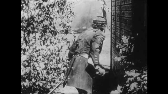 1910s: man falls down after explosion on yard. woman looks out window and cries. title card about wounded general. men carry soldier on stretcher into house. men place officer on sofa in living room.