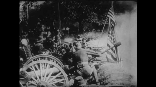 1910s: men in hats, Union uniforms and swords talk as line of cannons fire over wall. title card about hold the trenches. sick man on bed points and talks to military men in living room.
