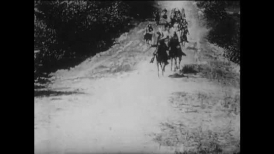 1910s: men on horses and wagons race down dirt road. Confederate troops creep near rocks. Blast at door knocks down Union soldiers in living room. Cannons fire on wall. title card about powder wagons.