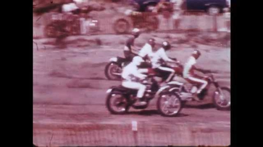 1970s: UNITED STATES: riders race over jumps on track. Rider in slow motion, Rider skids on bike. Racers on track