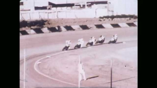 1970s: UNITED STATES: bikes race around circuit at track. Honda advert at race. Bikes jump over humps in race. Night racing.
