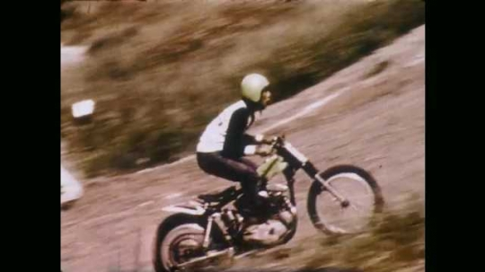 1970s: UNITED STATES: man rides bike up steep slope. Man comes off bike. Man slides down slope with bike.
