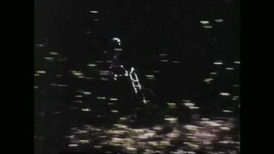 1970s: UNITED STATES: man rides motorbike along forest track. Rider does wheelie on bike.