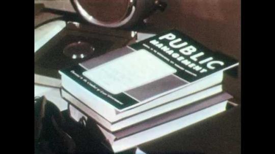 1950s: UNITED STATES: Public Management book on table. Man writes on blackboard with chalk. Tear gas gun. Resuscitation machine.