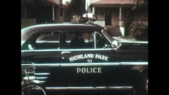 1950s: UNITED STATES: police officer by squad car. Policeman speaks on car radio.