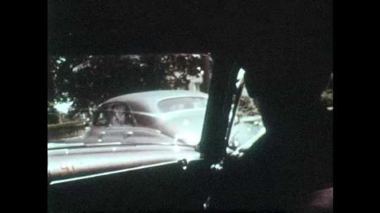 1950s: UNITED STATES: policeman in car. Policeman speaks with lady on doorstep of house. Officer speaks to people in street