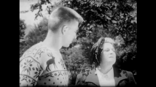 1950s: Young man in reindeer sweater and woman watch. Boys play football. Woman shakes her head and looks at young man. Woman and young man talk.