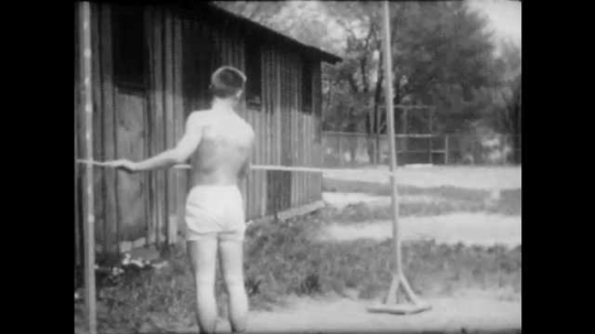 1950s: Young man positions crossbar for high jump and jogs away. Young man performs high jump, and puts his hands on his hips.
