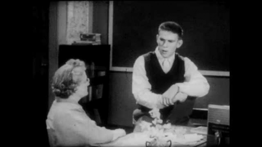 1950s: Young man in vest speaks to woman seated at desk in classroom. Woman at desk speaks and gestures. Young man sits down, speaks and smiles.