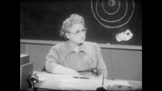 1950s: Woman speaks. Young man in classroom balls up piece of paper and throws it on floor, then shuts book and leans on his elbow. Young woman enters house and shuts door, leaving young man on stoop.