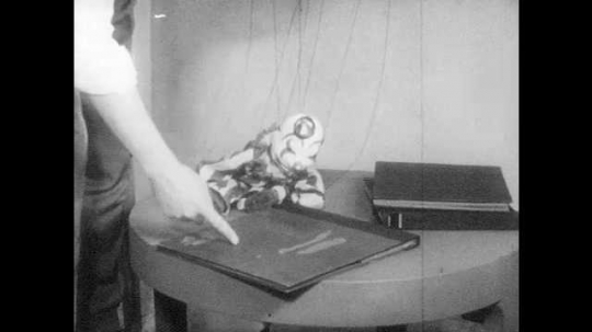 1950s: Man points at book.  Marionette nods head.  Man picks up book.  Puppet moves to the edge of the table and jumps off.