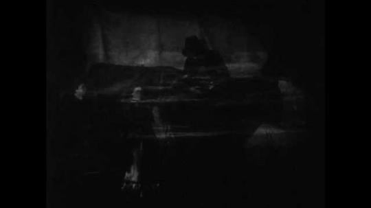 1940s: Men, women, and children sit around campfire at night. Man tunes violin, plays violin. People listen to music, boy smiles.