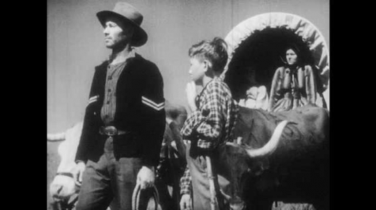 1940s: Man hold reins of bulls attached to wagon, talks to man on horseback. Woman and girl sit in covered wagon, watch men talk. Man on horse rides away, boy and man walk away, bulls pull wagon.