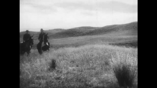 1940s: Two men ride horses through field, talk. Men dismount in front of sod house, walk to house. Woman walks around side of house, carries bucket.