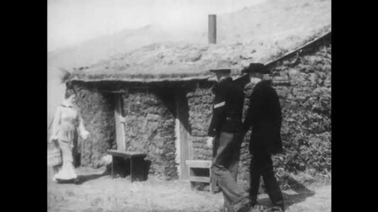 1940s: Two men walk up to woman outside sod house, take of hats, greet woman. Woman talks to men, enters house with bucket. Children carry sticks and branches. Two men sit outside house, talk.