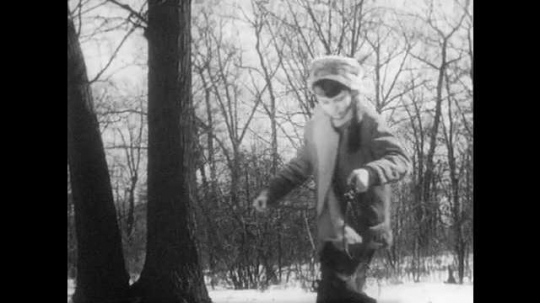 1940s: Boy in coonskin cap walks through snowy woods carrying bucket of coals. Boy enters cabin where Mother and sister stand by fireplace. Boy puts coals near the fireplace.
