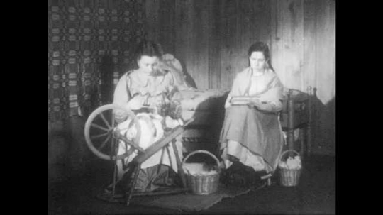 1940s: Mother spins wool as sister cards wool.
