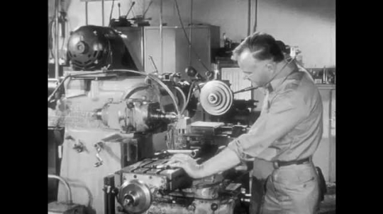 1950s: Man works industrial machine in factory. Man approaches, talks to man, man turns off machine, wipes hands, walks away.