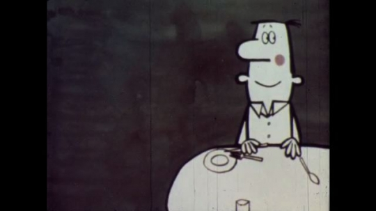 1960s: Animation: Man sits at dinner table, wife comes through door bringing onion rings. Man smiles, wags tongue, kisses fingers, pulls onion rings to himself.