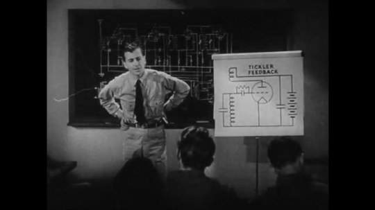 1940s: UNITED STATES: man stands at front of class. Man lectures students on circuits and grids.
