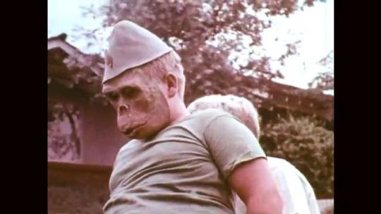 1960s: UNITED STATES: boys in monkey masks. Boy on handle bars of bike. Boy pedals