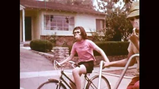1960s: UNITED STATES: Child on bike waves hand.