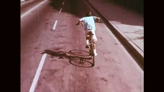 1960s: UNITED STATES: boy with tail rides bike through dark tunnel. Lights and reflectors title.