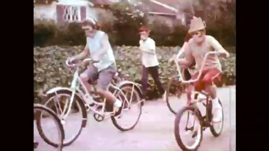 1960s: Children in monkey costumes ride bikes and run down street. Boy in mask stretches arms. Feet pedal bike. Text over boy in mask riding bike. Boy in monkey costume stops bike at crosswalk.
