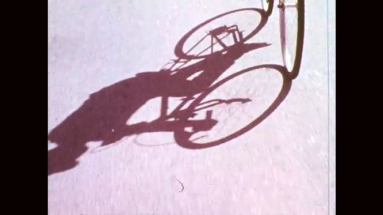 1960s: Shadow of bicycle. Car drives behind cyclist. Boy in monkey costume turns in front of car. Animated starbursts. Paper bag with text. Children in monkey costumes ride bikes and run down street.