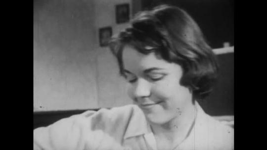 1950s: Woman speaks. Lady and man hug