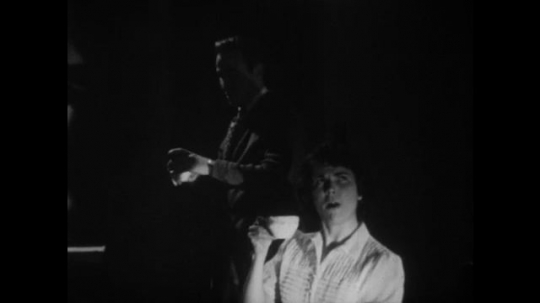 1950s: Woman sips coffee. Man turns down lights. Man sits down with coffee cup. Man and woman speak, clasp hands and kiss.