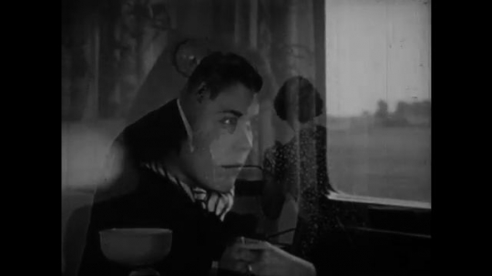 1950s: Woman seated on train looks around.