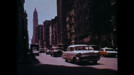1960s: Car drives down city street. Man sits behind desk at union office, looks at papers. VW beetle drives up to house, child runs to meet car.