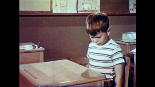 1950s: Boy uses hand to measure desk in classroom, smiles, opens desk.