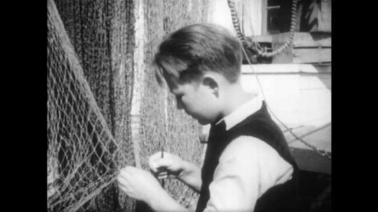 1940s: Boy fixing fishing net. Boat docked in harbor. Man and boy inspect rope on boat.