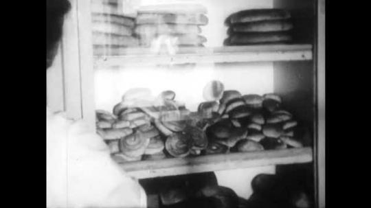 1940s: Woman opens cabinet, puts rolls in bag. Children exit building.