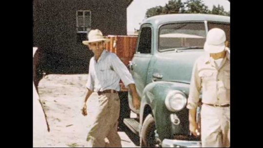 1950s: Man in hat walks away from parked truck, up ramp to building. Man in hat talks on telephone in office, then hangs up phone. Man in hat gets into truck and drives.
