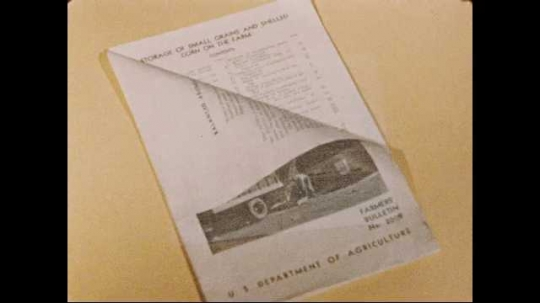 1950s: Pamphlet lays on table. Hand turns page of pamphlet. Words appear over pages of pamphlet providing information on maintaining crops after harvest. Man in hat hangs sign on wall.
