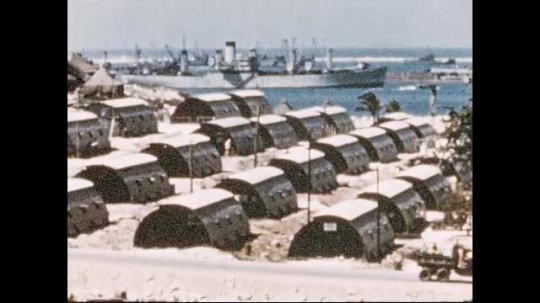 1950s: Rows of storage buildings on beach at Navy yard. Fire burns around storage building.