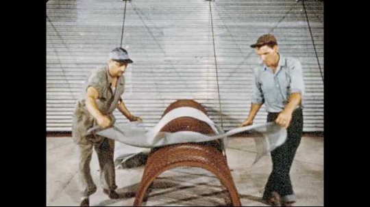 1950s: Two men cover tube-like metal cage inside building. Grain is dumped over covered cage. Animated diagram of grain in granary with fan inside and lines escaping to the top.