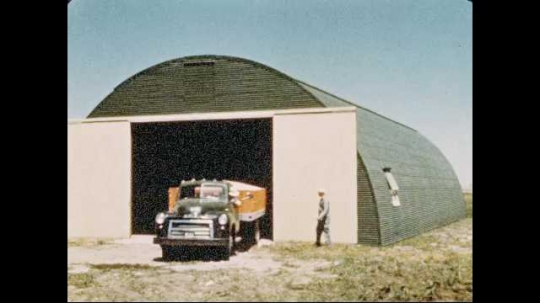 1950s: Dump truck hauling grain backs into storage building, guided by man.