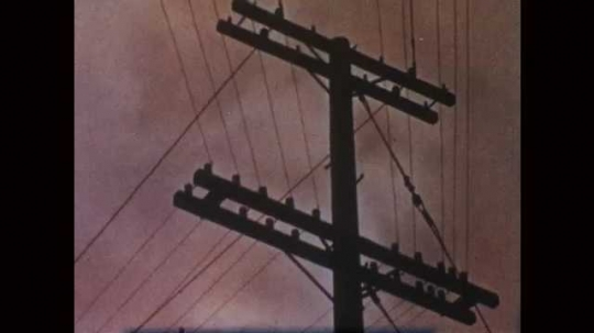 1950s: Storm clouds behind a utility pole. Water exiting downspout/gutter. Boots walking through wet street. Puddle in a gutter. Rain falling on storm grate. Clouds and lightning.