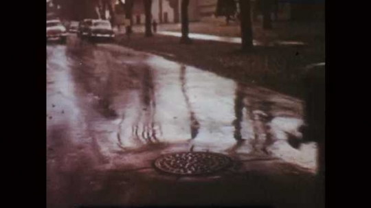 1950s: Car driving down suburban street in the rain. Rain falling on plants. Cars in traffic in the rain, windshield wipers. Girl on patio of house opens paper bag.