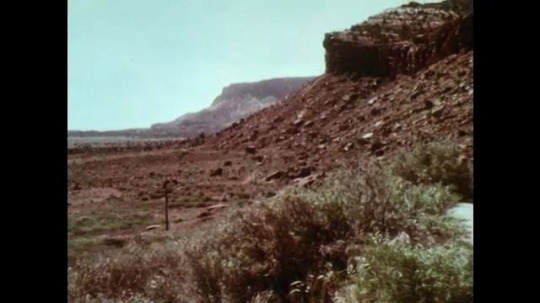 1970s: Rocky desert landscape with small stone house. Wooden electrical pole. Small stone house with American flag. American flag waves through trees.