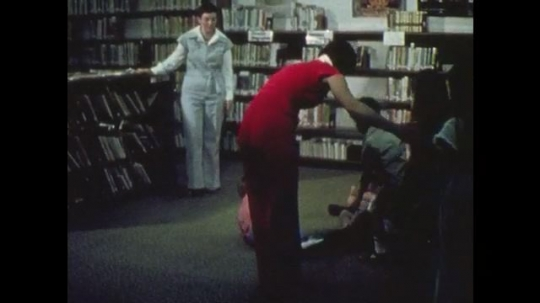 1970s: Woman seats children on floor. Woman speaks to kids