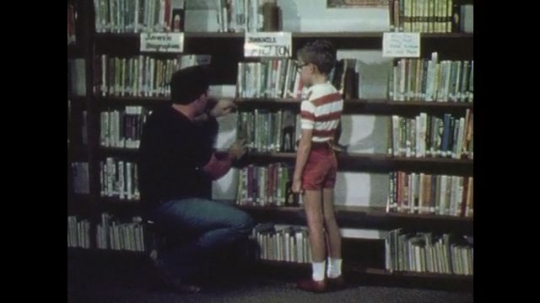 1970s: Man selects book and talks to boy